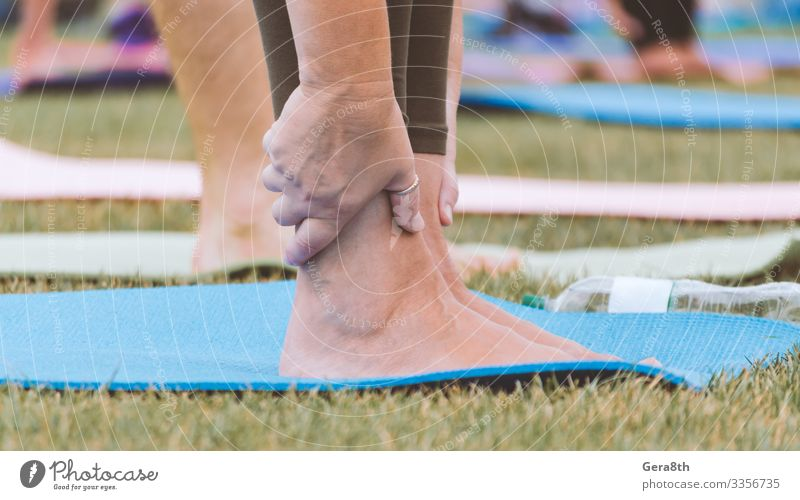 female legs on yoga mat close up Bottle Skin Summer Sports Yoga Woman Adults Hand Fingers Group Nature Grass Park Street Railroad Fresh Green Colour Action