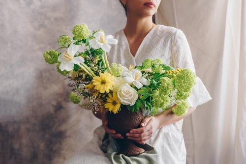 Young woman in a white dress holding vase with flowers. Lifestyle Elegant Style Happy Beautiful Chair Wedding Woman Adults Lips Hand Flower Dress Brunette