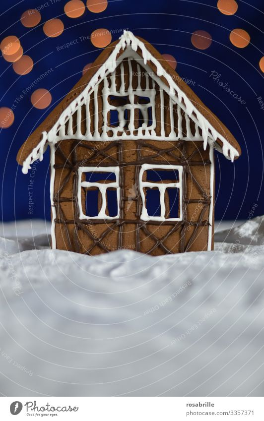 Gingerbread house facade with icing and chocolate decoration as half-timbered on white velvet, which looks like snow, in front of a dark blue background with bokeh dots as stars
