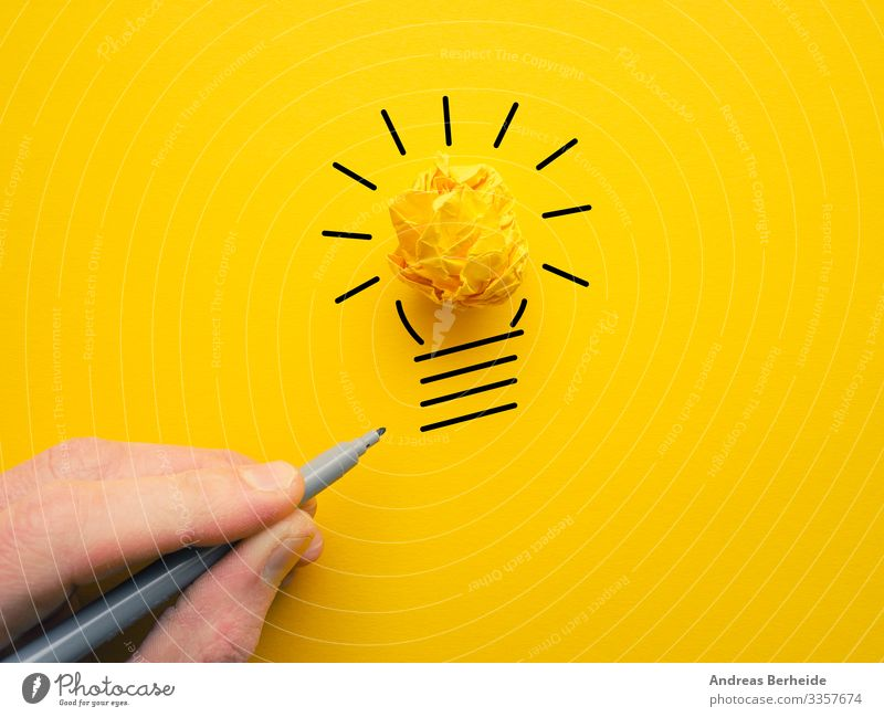 Yellow crumpled paperball as lightbulb hand idea lamp energy concept drawing businessman power electricity bright innovation symbol creativity ideas finger