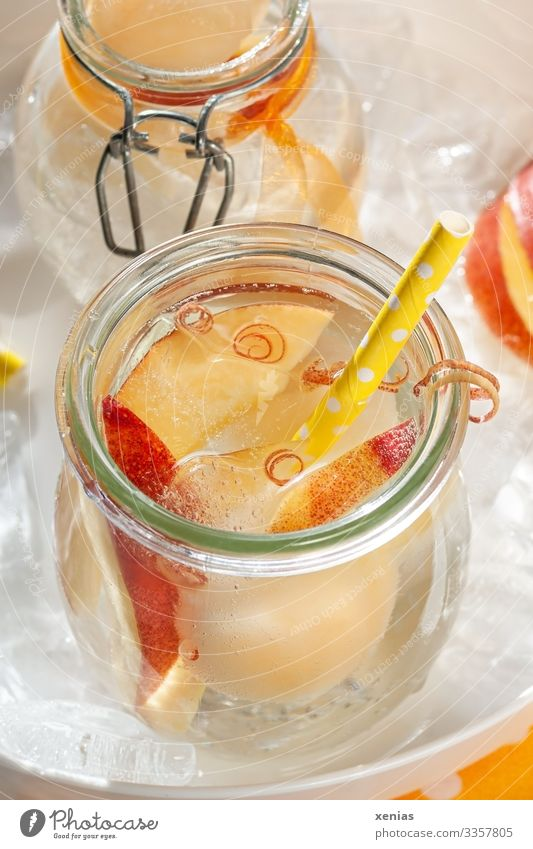 Cool lemonade with juicy nectarine in glass and yellow drinking straw on a white tray full of ice cubes Cold drink fruit Nectarine Beverage Ice cube Vitamin