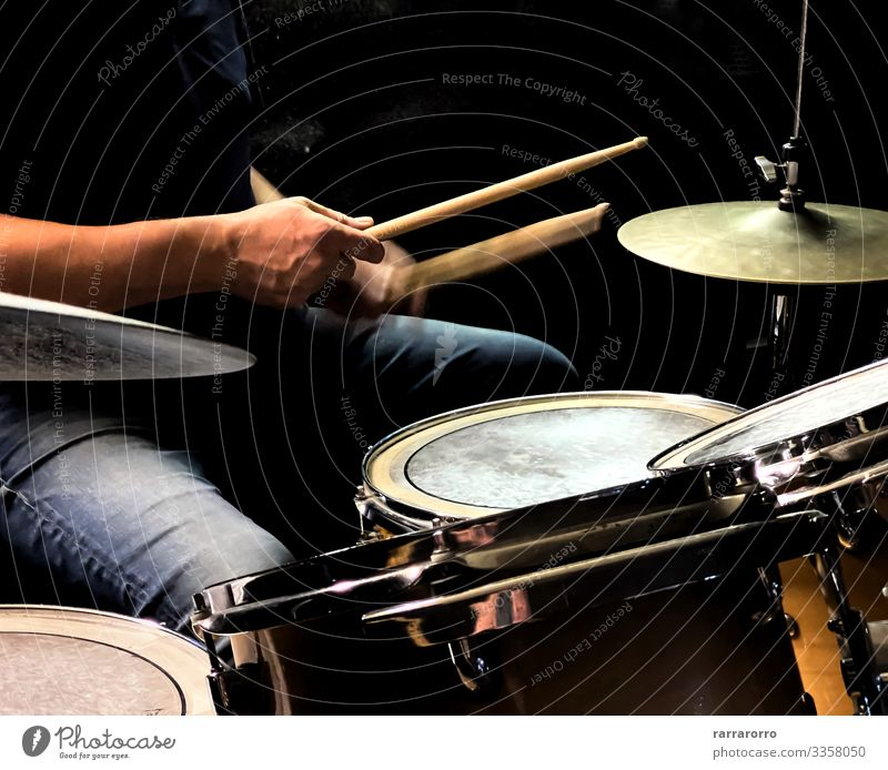 a drummer while playing the drums Playing Entertainment Music Human being Man Adults Hand Concert Band Musician Drum set Rock Metal Dark Modern Black action