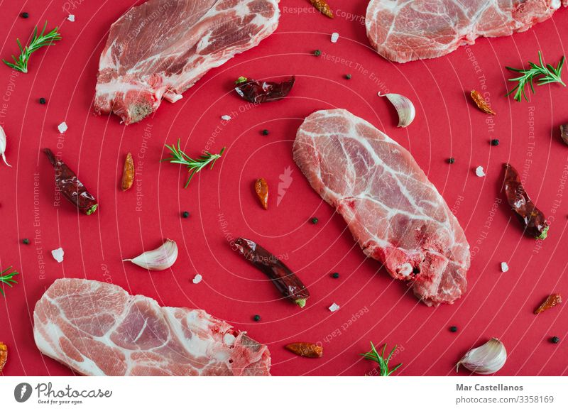 Raw meat steaks with spices on red background. Flat lay. Meat Herbs and spices Nutrition Eating Dinner Diet Feeding Fresh Juicy Green Red Advertising Pork