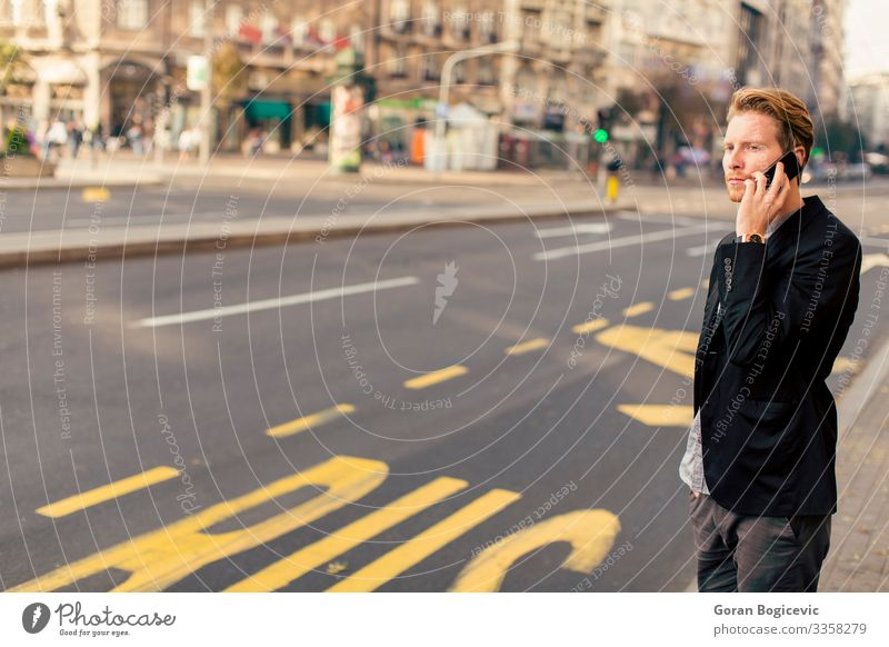 Young man on the street with mobile phone Lifestyle Telephone PDA Technology Human being Youth (Young adults) Man Adults Facial hair 1 18 - 30 years Autumn