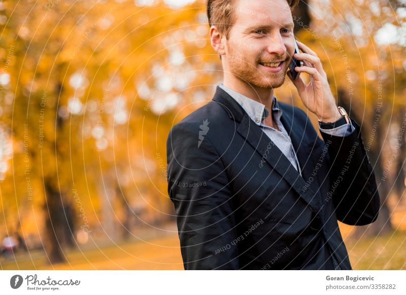 Young man with mobile phone in the autumn park Lifestyle Style To talk Telephone PDA Technology Human being Youth (Young adults) Man Adults 1 18 - 30 years