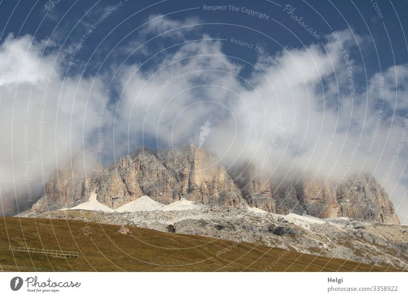 Mountains of the Alps are wrapped in thick clouds of blue sky Dolomites Sella yoke Autumn Meadow Clouds Sky Hiking Mountaineering Environment Nature Landscape