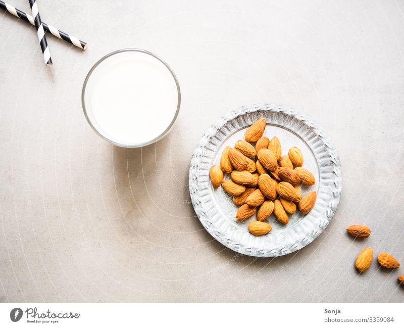 A glass of almond milk and a plate of almonds Food Dairy Products Almond Nutrition Breakfast Organic produce Vegetarian diet Diet Beverage Milk Plate Glass