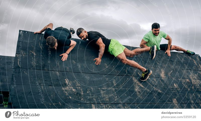 Participants in obstacle course climbing wall Lifestyle Sports Climbing Mountaineering Human being Man Adults Group Authentic Strong Black Effort Energy