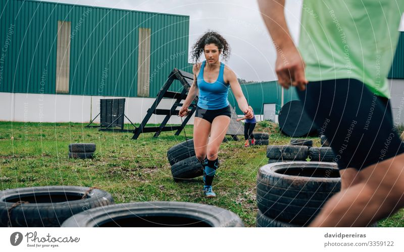 Participant in an obstacle course dragging wheels Sports Human being Woman Adults Man Grass Authentic Strong Power Effort obstacle course race Runner pulling