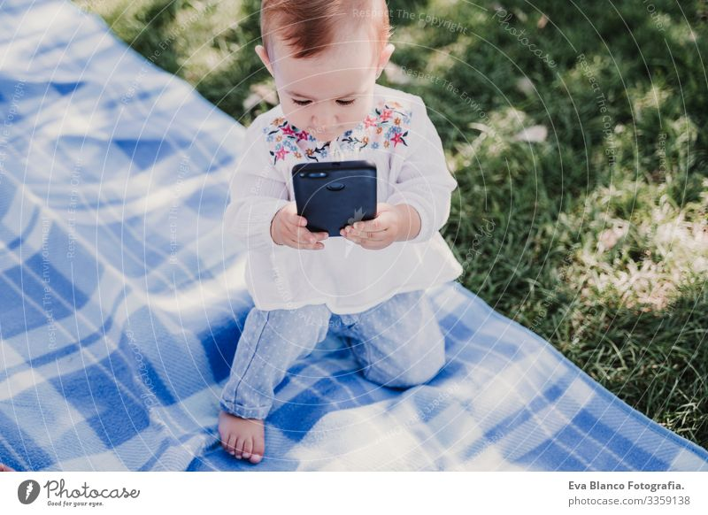 happy baby using mobile phone outdoors. technology concept Mother Baby Cellphone Technology Together Child Parenting Girl Joy Sunbeam Parents Spring parenthood