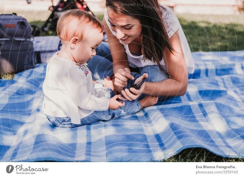 young mother and happy baby using mobile phone outdoors. technology concept Mother Baby Cellphone Technology Together Child Parenting Girl Joy Sunbeam Parents