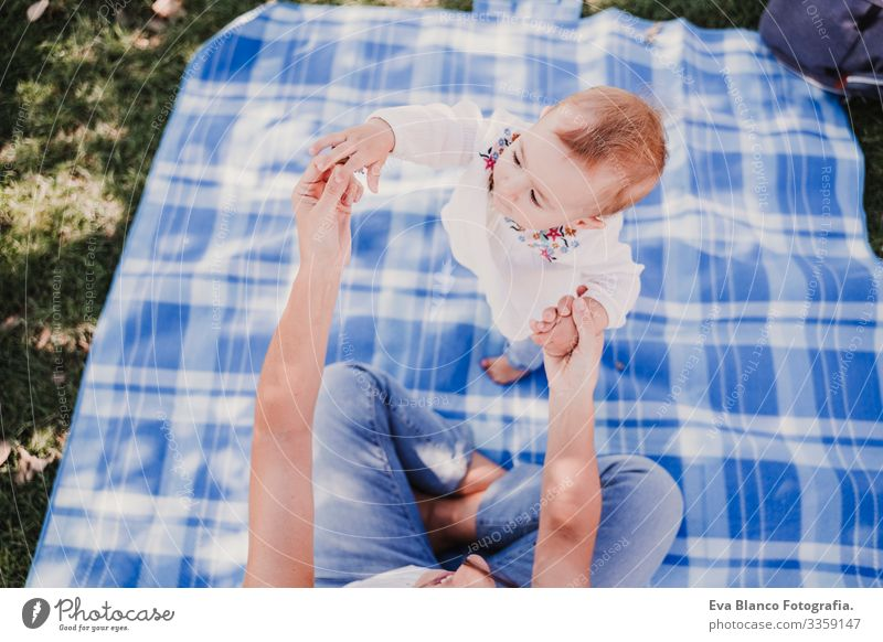 young mother playing with baby girl outdoors in a park, happy family concept. love mother daughter Child Parenting Girl Joy Sunbeam Parents Mother Spring Baby