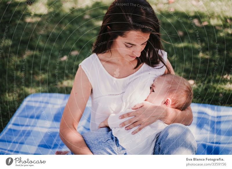 young mother playing breast feeding her baby girl outdoors in a park, happy family concept. love mother daughter Mother Baby Appease Milk Eating Child Parenting