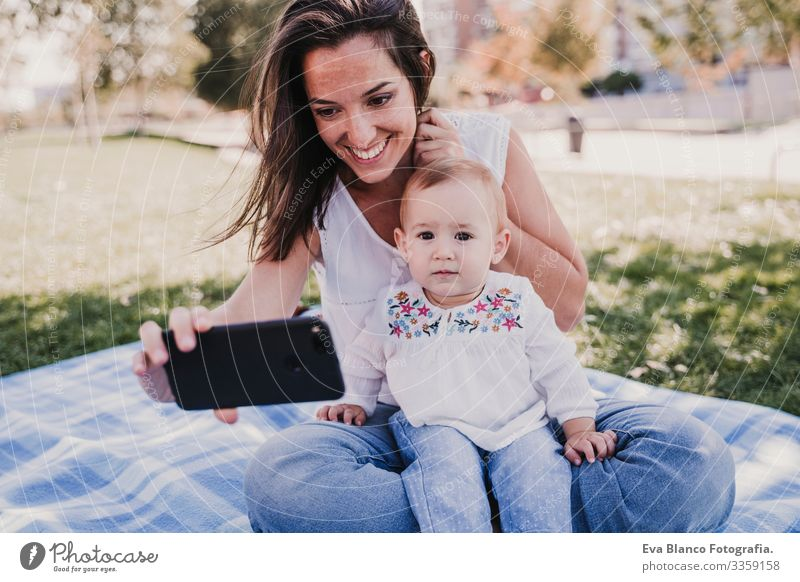 young mother and happy baby using mobile phone outdoors. technology concept Child Parenting Girl Joy Sunbeam Parents Mother Spring Baby parenthood candid
