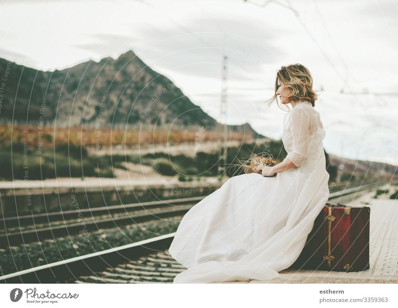 Pensive bride with a red suitcase on the train tracks Lifestyle Elegant Style Beautiful Vacation & Travel Adventure Freedom Wedding Human being Feminine