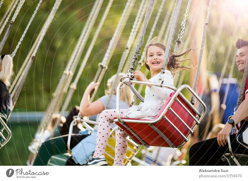 Little girl having fun on chain carousel. Happy summer memories. Carefree childhood and happiness action activity adventure amusement beautiful cheerful circle