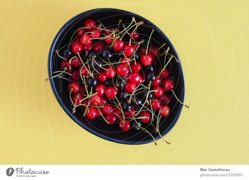 Black ceramic bowl with wild cherries on yellow background. Food Fruit Dessert Nutrition Vegetarian diet Diet Bowl Healthy Eating Wellness Summer Nature