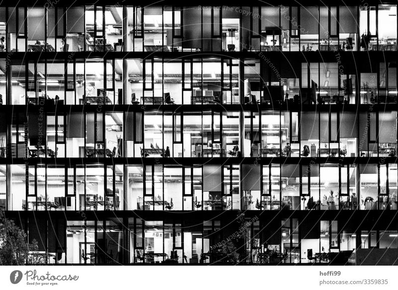 illuminated offices of a high-rise building in the evening - closing time High-rise Office work Closing time Illuminated Bank building Facade Capital city