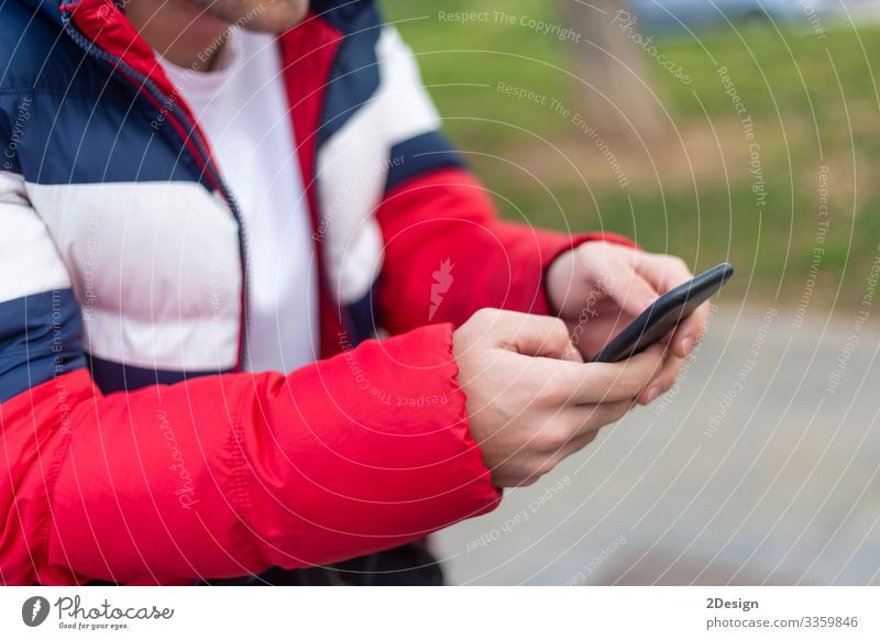 Young man with smartphone in hand texting outdoors in the street mobile holding using technology mobile phone device message cyberspace digital male person