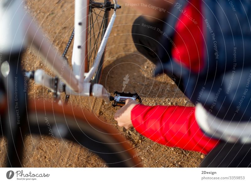 Young Man repairing his bicycle outdoors in th street grown-up young adult outside bike mountain biking track ride nature person activity caucasian chain