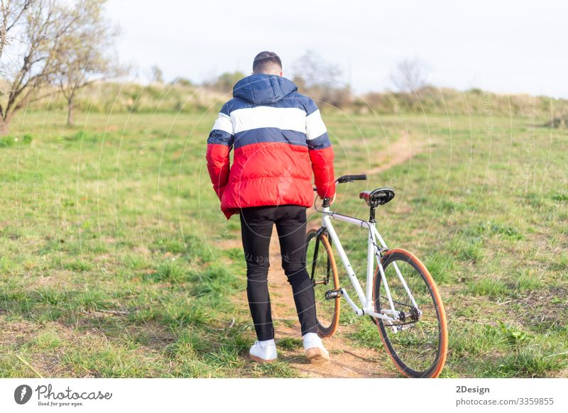 Rear view of a young man walking on a park with a fixed bike Lifestyle Style Happy Leisure and hobbies Music Telephone Cellphone PDA Technology Human being
