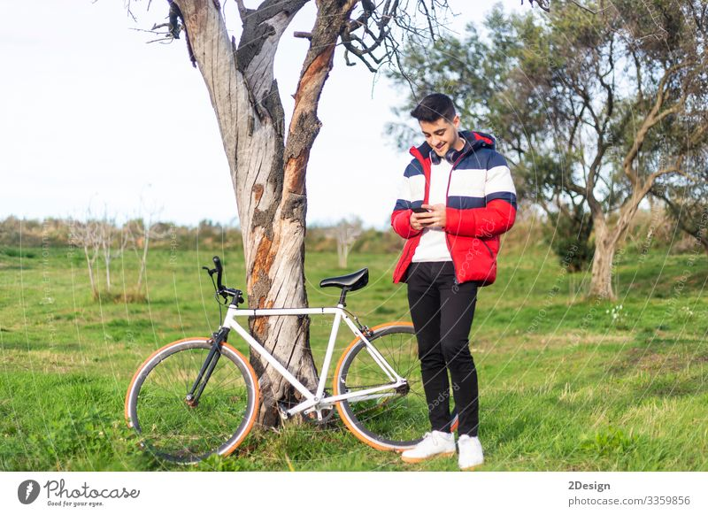 Handsome hipster young man enjoying a bicycle ride and using a smartphone while walking on park street bike people male person earphones outdoors city fixie