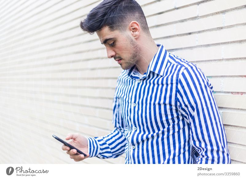 Young happy man leaning on house wall while using his smartphone Lifestyle Style Happy Business Telephone Cellphone PDA Technology Human being Masculine