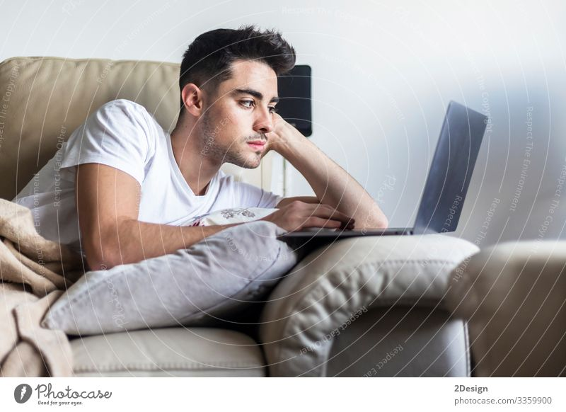 Young man relaxing on sofa while using laptop Lifestyle Happy Relaxation Leisure and hobbies House (Residential Structure) Sofa Living room Work and employment