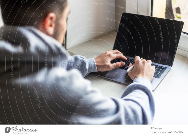 Rear view of a young man working with laptop on desktop at home Decoration Desk Table Work and employment Workplace Office Business Computer Notebook Screen