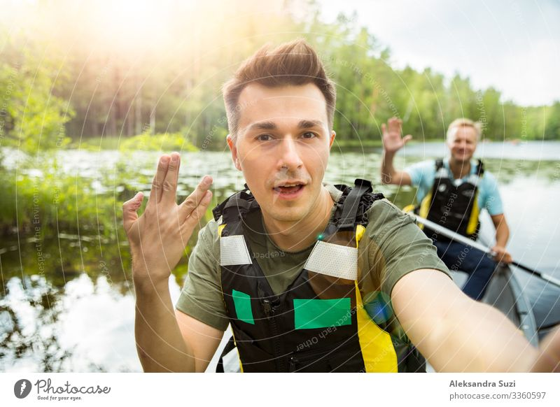 Two men in life vests canoeing in forest lake. Action Adventure Canoe Destination Discover Finland Forest Happy Vacation & Travel Lifestyle Man Nature