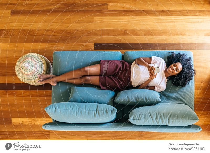 Black woman chatting on smartphone lying on couch at home using chill lounge sofa living room modern relax african american black rest browsing mobile smile