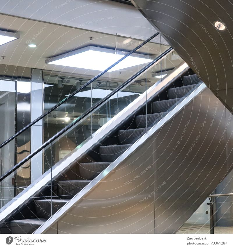 standstill Shopping malls Trade Business Escalator Ceiling light Glass Metal Sharp-edged Cold Town Gray Silver White Disciplined Boredom Loneliness Stagnating