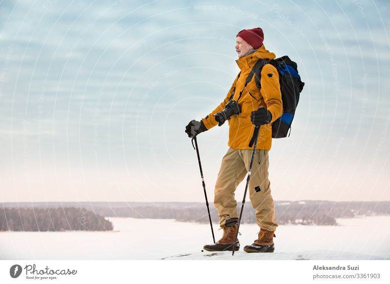 Portrait of mature man with grey beard exploring Finland in winter. Traveler with camera on the top of rock. Beautiful view of northern landscape with frozen Baltic Sea and snowy islands.