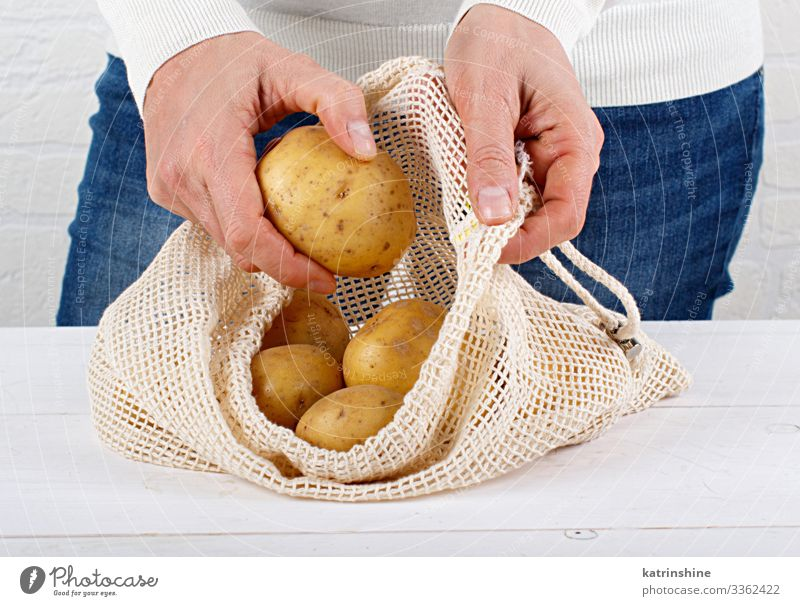 Woman put fresh potatoes in a textile bag Food Vegetable Lifestyle Shopping Adults Hand Environment Plastic Free Natural White Zero waste Conceptual design