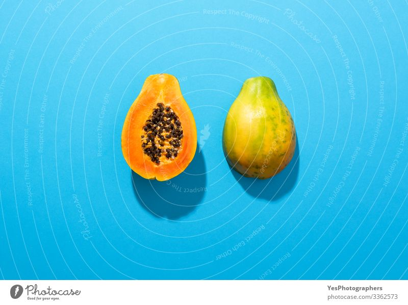 Ripe papaya fruit cut in half on blue background Food Fruit Dessert Nutrition Organic produce Healthy Eating Fragrance above view Blue background colorful