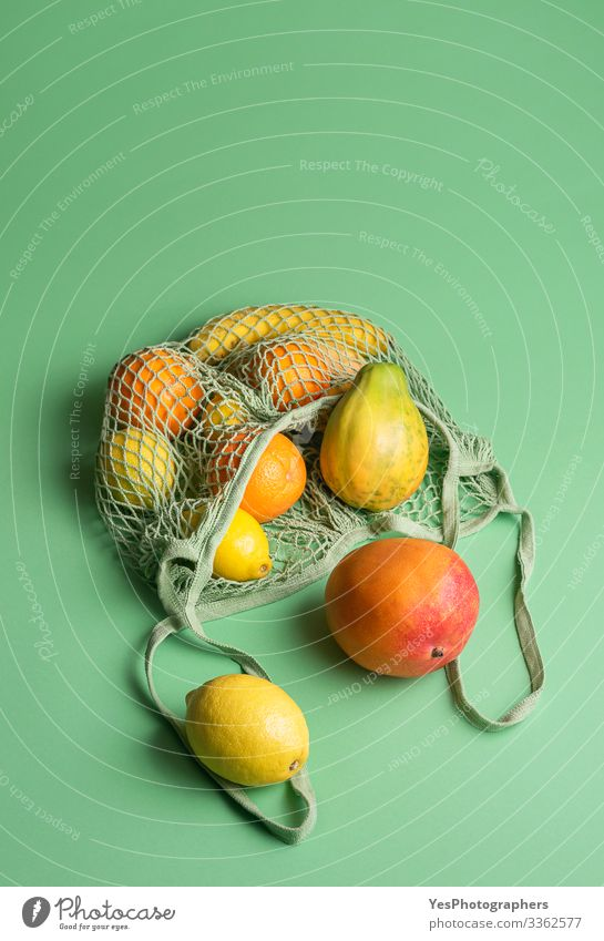 Ripe tropical fruits in a net shopping bag. Buying fruits Fruit Orange Healthy Eating Green above view buying fruits colorful diet food eco-friendly packaging