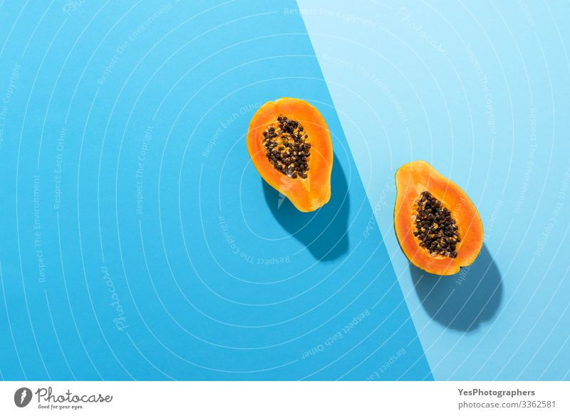 Fresh papaya fruit cut in half on blue background Fruit Dessert Organic produce Healthy Eating Juicy above view Blue background blue shades colorful diet food