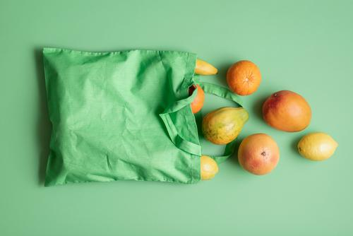 Bag of tropical fruits. Food shopping. Eco-friendly bag Fruit Orange Organic produce Vegetarian diet Healthy Eating Green above view buying fruits colorful