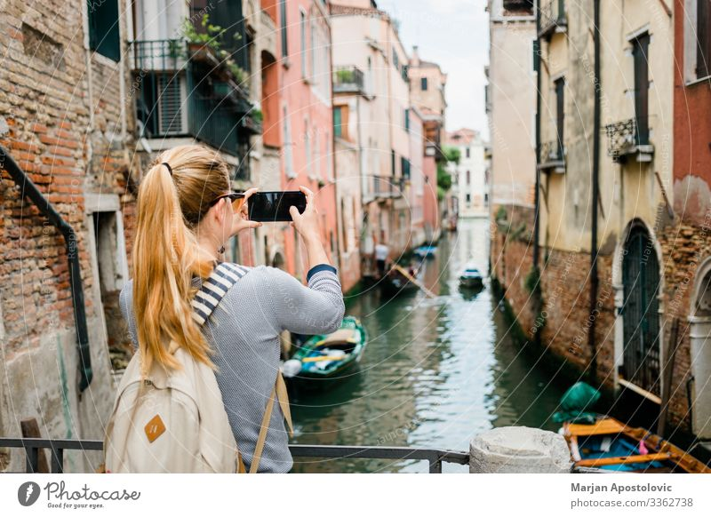 Young woman taking a photo of a canal in Venice Lifestyle Vacation & Travel Tourism Trip Sightseeing City trip Cellphone Human being Feminine