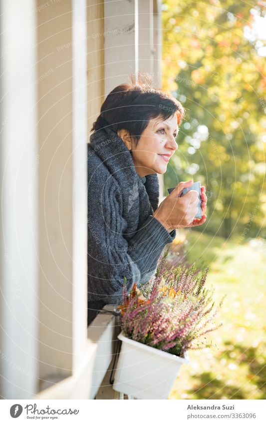 Mature attractive woman with cup of hot coffee Autumn Beautiful Cheerful Clothing Coffee Cold Safety (feeling of) Comfy chair Hut Cottage Cozy Cup Beverage