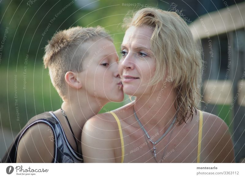 Son kisses his mother on the cheek Family Young woman Trust Contentment Safety Safety (feeling of) Loyal Protection Love Calm Colour photo Authentic Day
