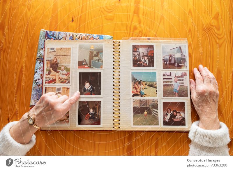 Top view of a senior caucasian woman looking at an old photo album themes of memories nostalgia photos retired picture elderly wife together pensioner family