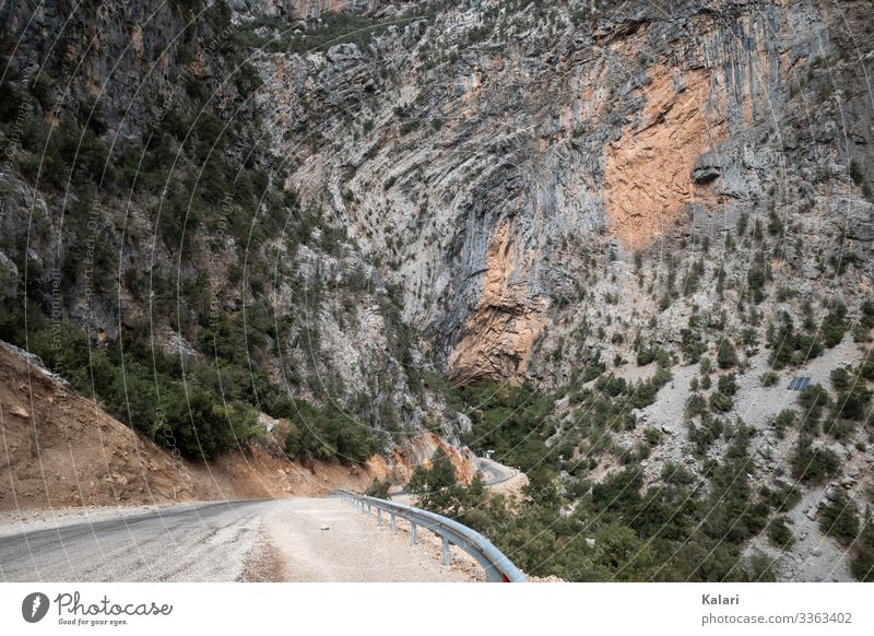 Winding road in the mountains leads to a rock face Street Wall of rock Trip route off Landscape Sparse panorama Nature Sky Turkey Blue arrive Summer Desert view