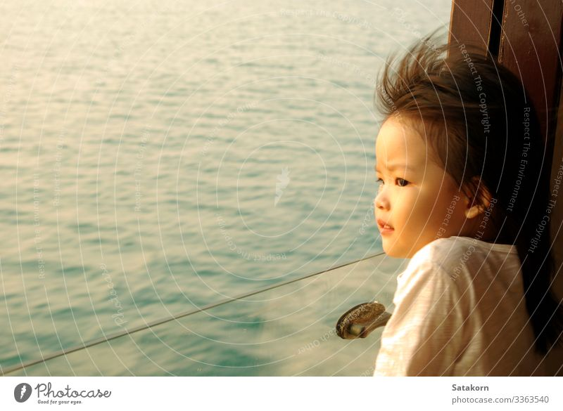 Asian girl stares out of the passenger boat window Lifestyle Summer Ocean Human being Child Girl Face Eyes 1 3 - 8 years Infancy Water Wind Waves Passenger ship