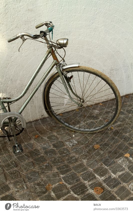 alt l old, nostalgic wheel in retro style, parked in front of a white, bright house wall on cobblestone. Front part, handlebar, lamp, light, tires, brake of grey wheel parked in the city. Risk of theft of old bike, not locked.