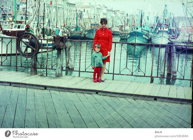 Happy, fashionable, stylish mother with daughter at hand, in partner look, are on holiday in the 60's, during a stroll through the city; trip on a bridge in the port of Venice, with water, ships and boats in the background.