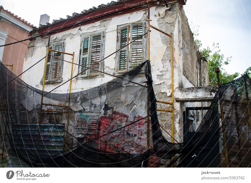 Demolition house secured with net condemned house safety net Protection Sky Facade Scaffolding Window Architecture Long shot Deep depth of field Sunlight
