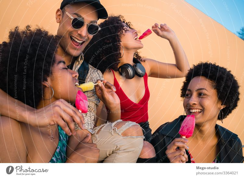Multi-ethnic group of friends enjoying summertime while eating ice cream. multiethnic friendship young people dessert diversity diverse pleasure man woman