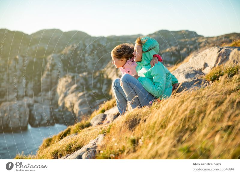Two little girls play on rocky northern seashore. Action Adventure Recklessness Friendliness Cheerful Infancy Child Dawn Europe Fjord Friendship Joy Happiness