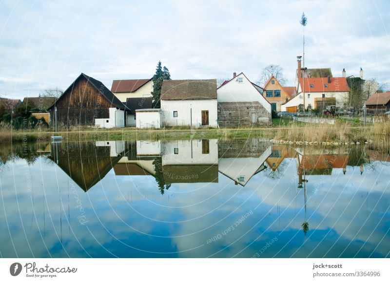 Rural franconian houses situated at an idyllic pond which are reflected in it Franconia carp pond Sky Clouds Winter Reflection Calm Environment Small Town Idyll
